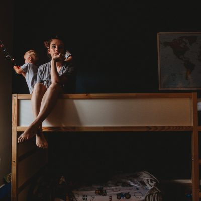 a self portrait ofa mom sitting on a bed with two boys playing around her