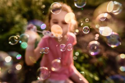 Girl blowing bubbles in backlight during gloden hour creates bokeh