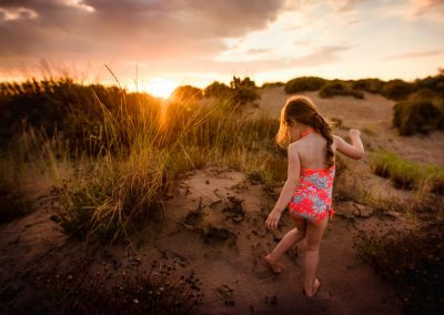 girl stands on prickly dune plants on the beach at sunset