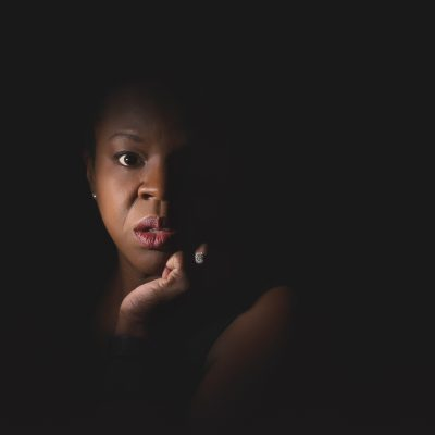 African American woman in split lighting with diamond ring.