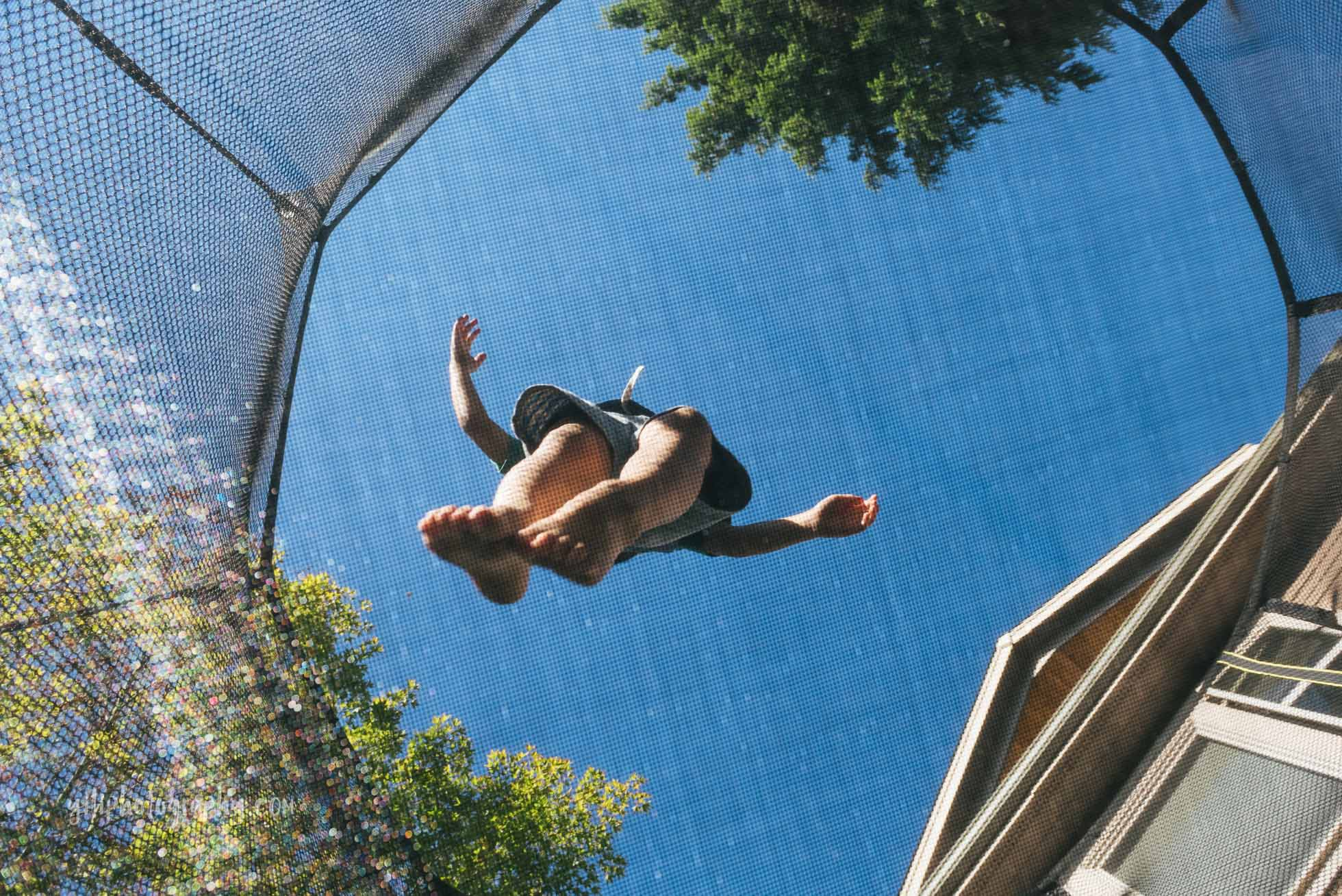 view of little boy bouncing on trampoline shot from below