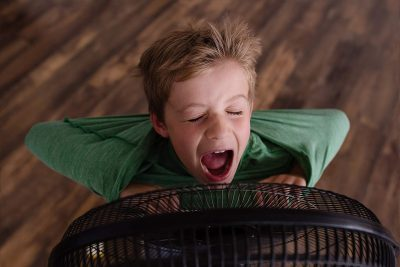Boy screaming into fan