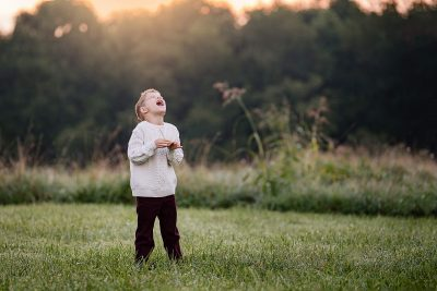 Boy laugh in field sunrise