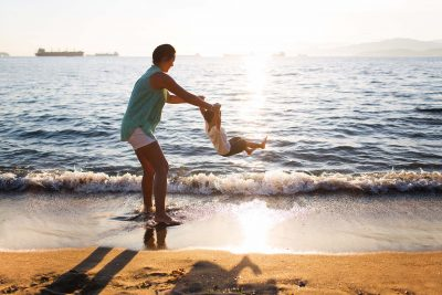 Mother and son playing by the ocean waves