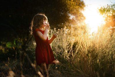 Little girl red dress field of weeds