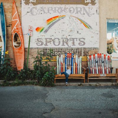 Boy climbs bench made of skis with colorful background of mural and kayaks in downtown Salida Colorado