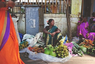 A lady sits selling vegetables at a street market in Goa, India, by Kirsty Larmour
