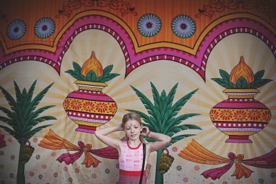 A girl stands beside a brightly coloured screen after visiting the temple and receiving blessing, by Kirsty Larmour