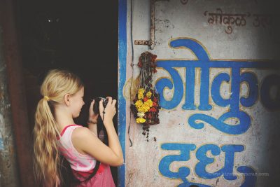 A child photographs some decaying offerings on a street in India, by Kirsty Larmour