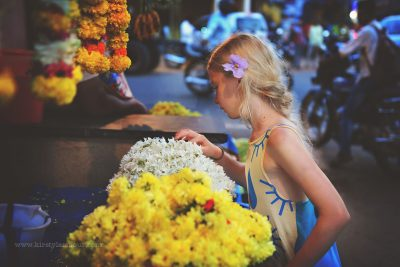 A girl chooses flower garlands from a stall in an Indian market, by Kirsty Larmour