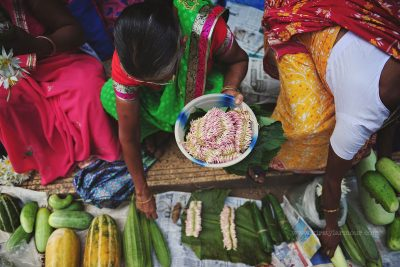 A lady sells both flower garlands and vegetables on the roadside in a street market in Goa, India by Kirsty Larmour