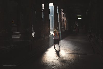 A girls walks through light streaming in from a temple roof in India