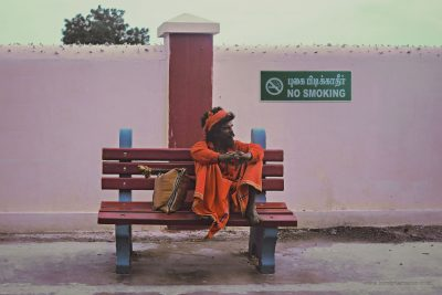 """A religious man sits beneath a """"No Smoking"""" sign on a station in India, by Kirsty Larmour"""
