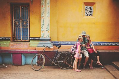 a family takes a rest beside a colourful temple in Southern India