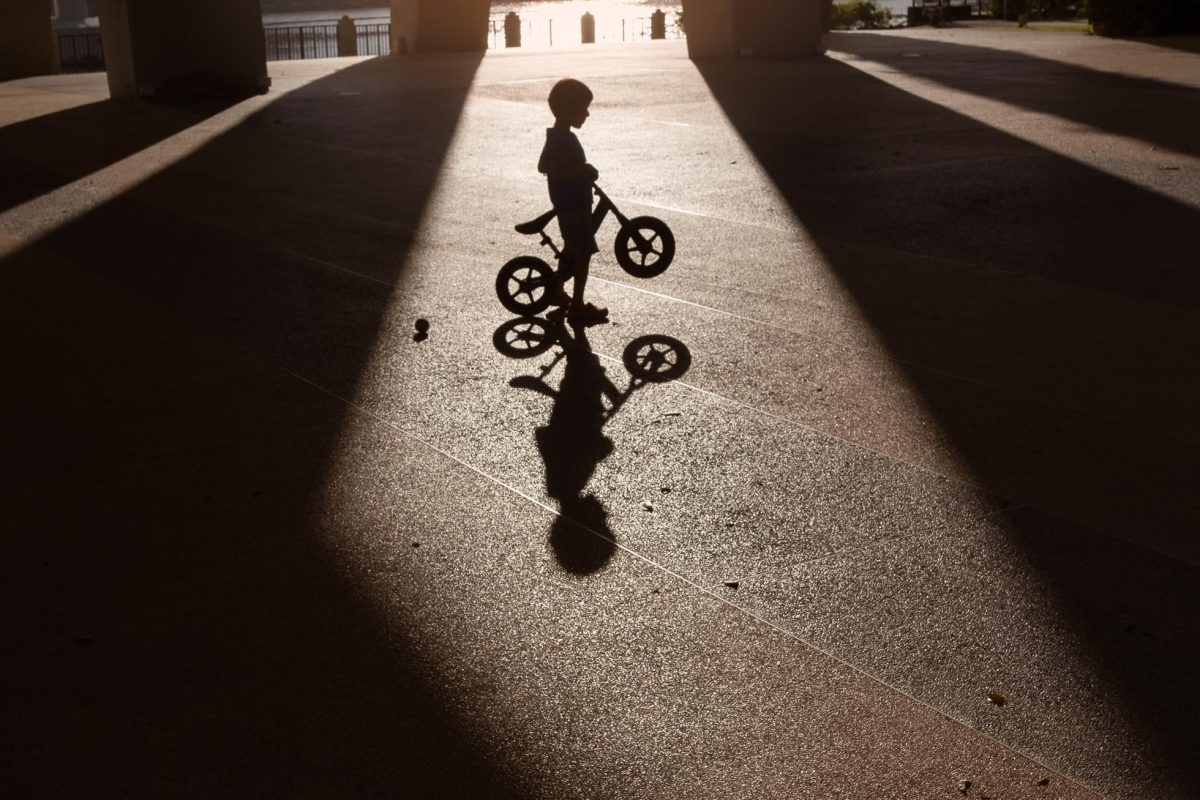 child framed in shadows with his bike