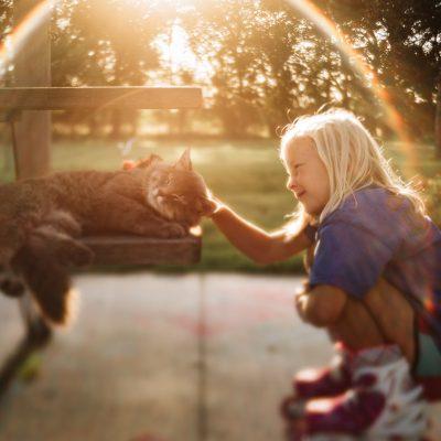 girl petting cat lens baby