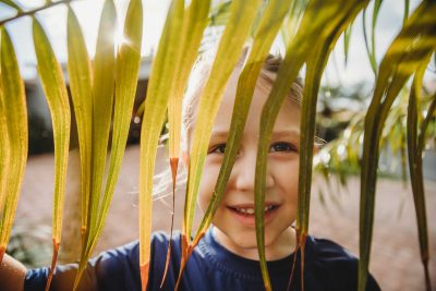 girl playing with palm tree leaf snapberry photographs