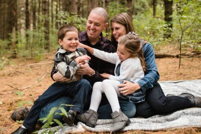 family of four laughs together in pine forest