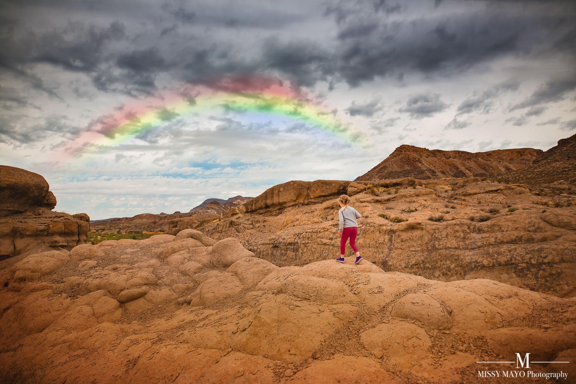 little girl running on rocky mountains towards a rainbow