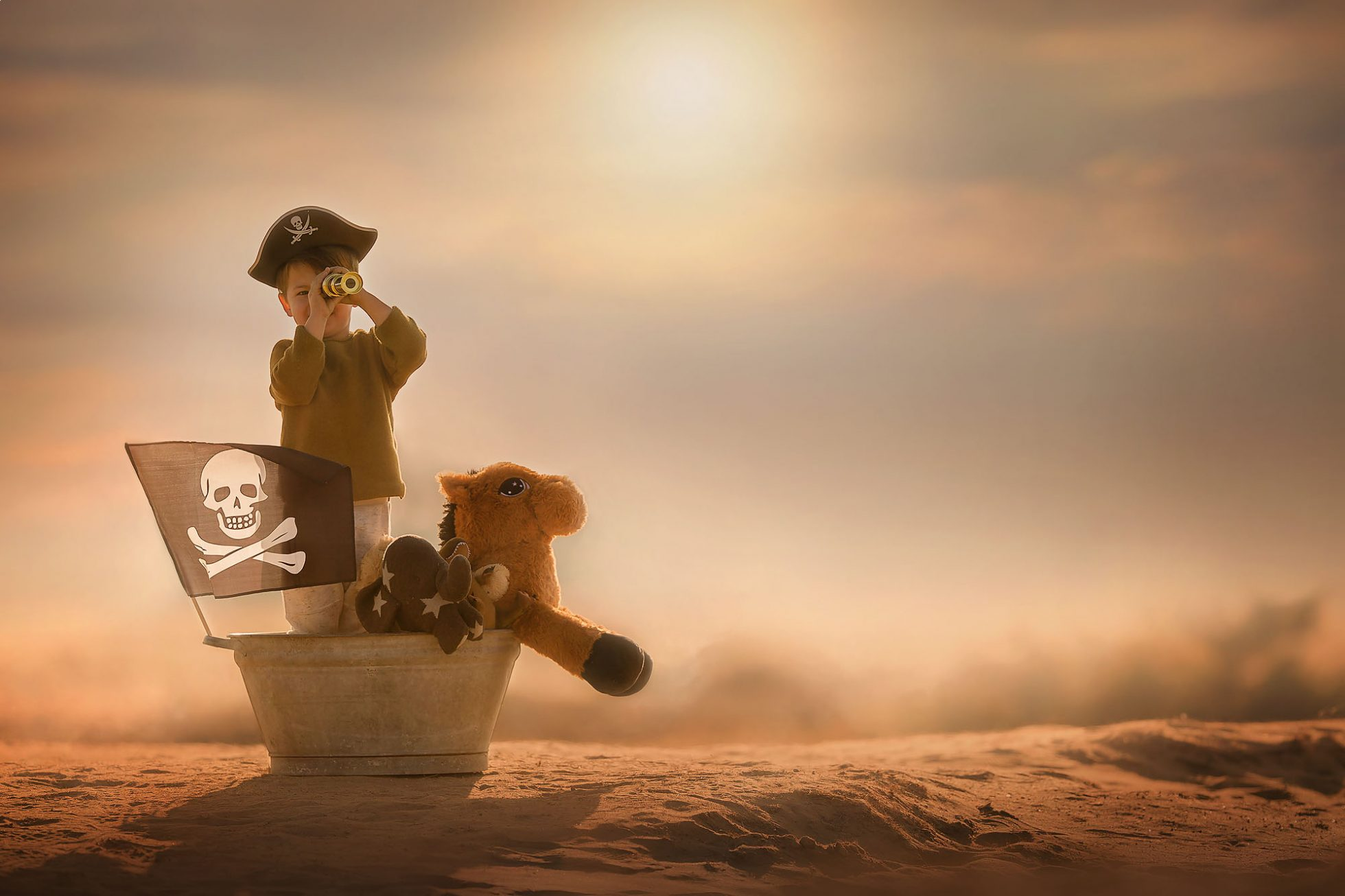 Canon 5D mark III Color image of a little boy pirate standing in a bath tub with toy animals and binoculairs in the desert during sunset by Willie Kers