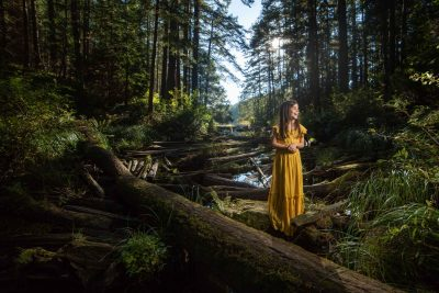 Girl in yellow dress standing on a log in a forest