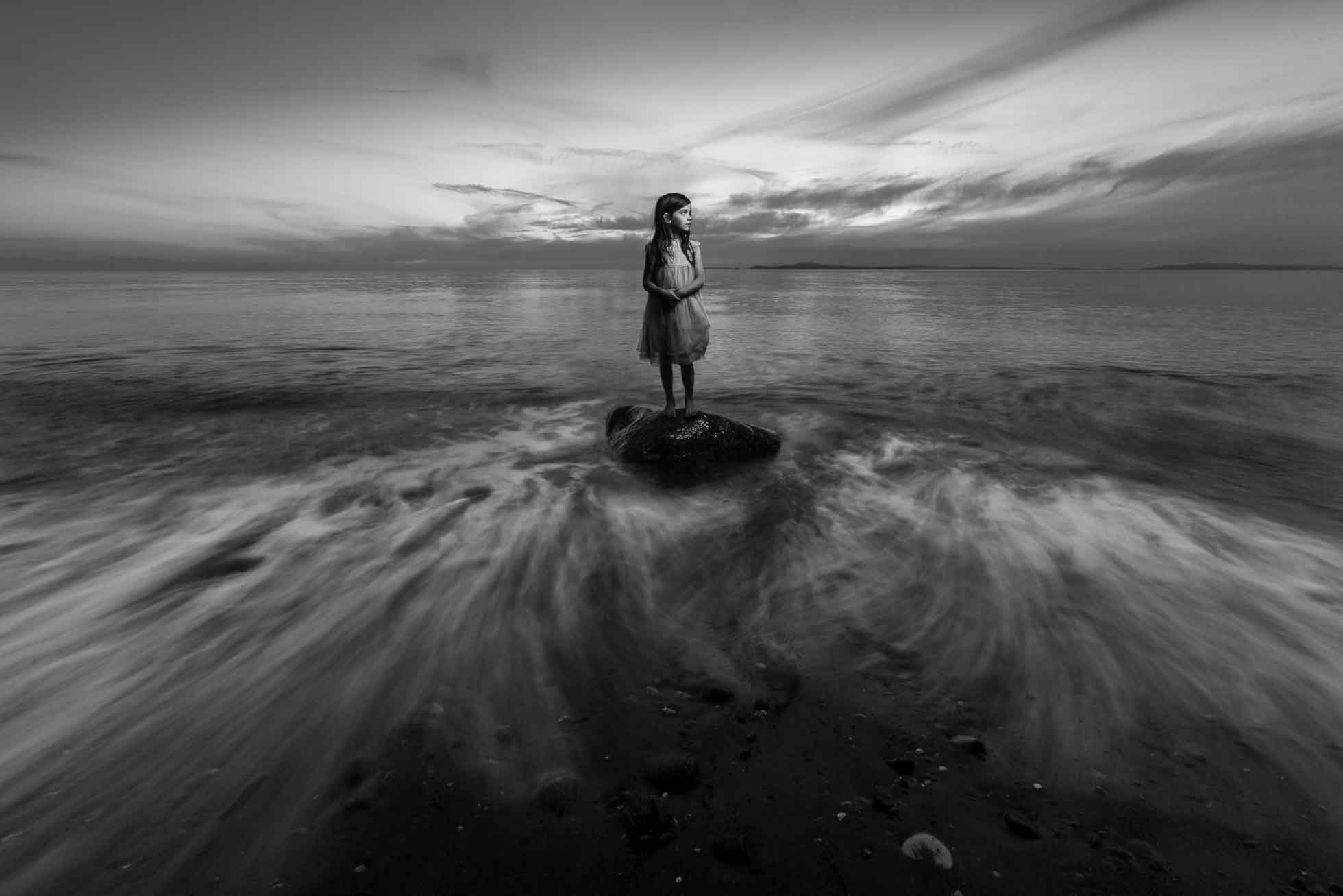 Girl standing on a rock in the water