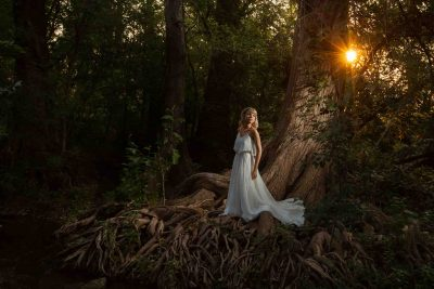 Woman standing on creek near cypress tree