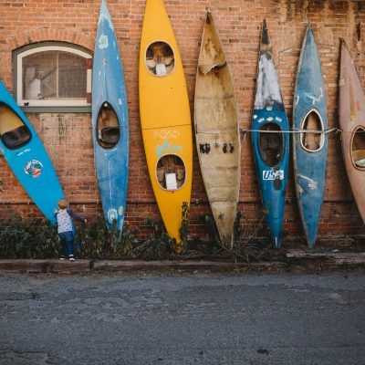 Boy touching a blue kayak in a line of colorful kayaks in downtown Salida Colorado