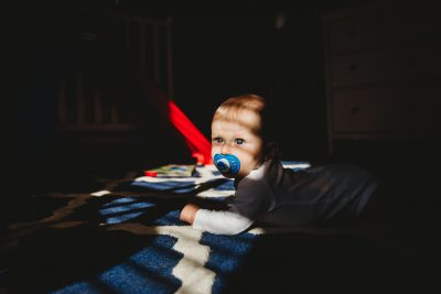 Baby boy plays on floor as shadows hit face and light illuminates his blue eyes