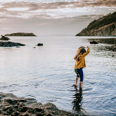 Little girl dancing in the water near Deception Pass, Washington.