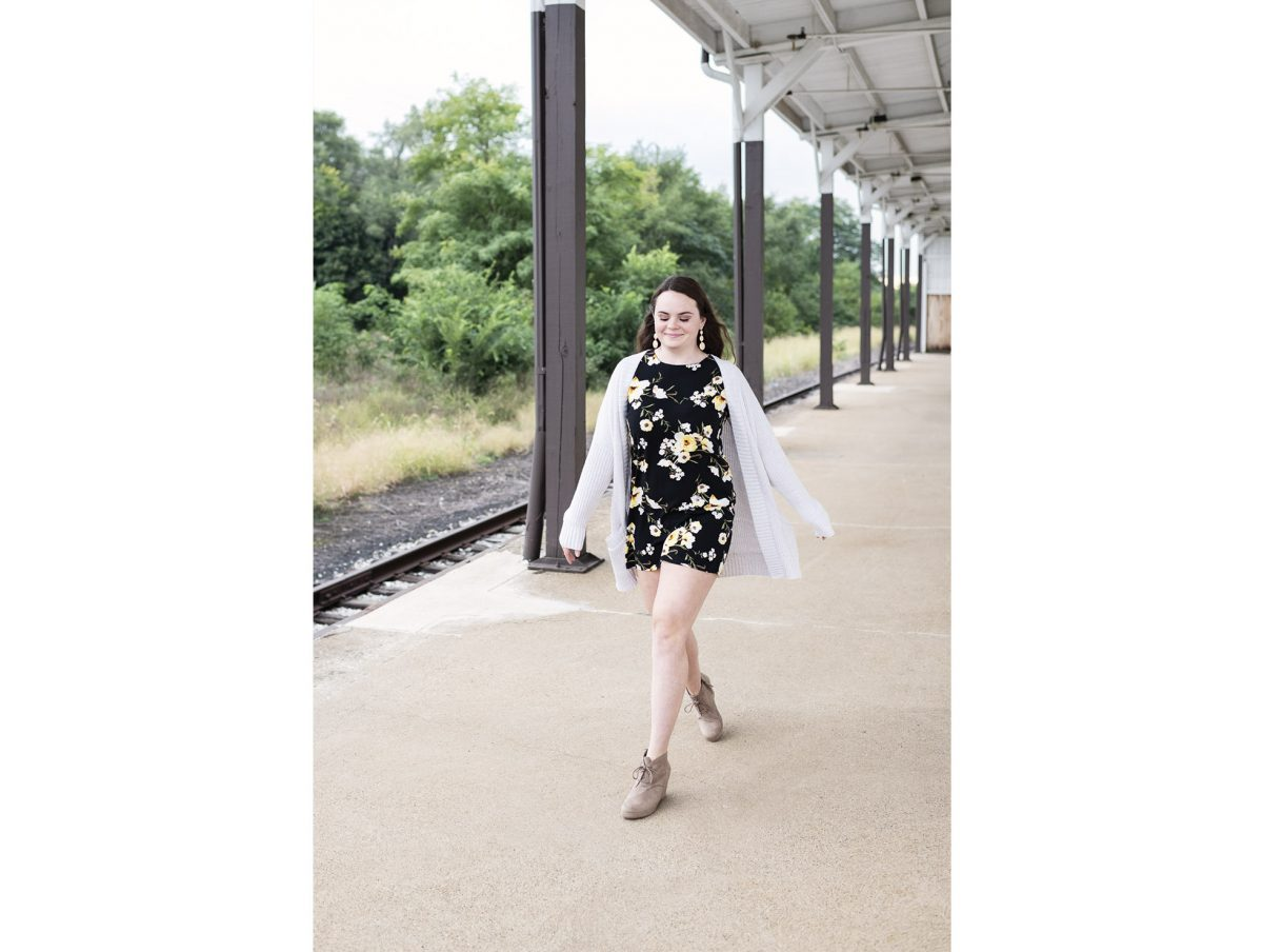 A senior girl walks along a railroad platform with energy and conviction.