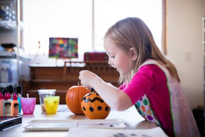 girl in pink painting orange pumpkin with black dots