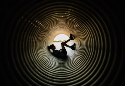 boy is resting in a giant tunnel at a pumpkin patch farm lifestyle photographer