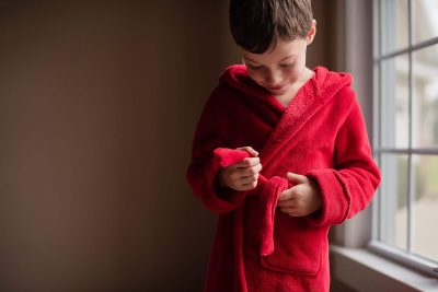 boy in red robe by window light