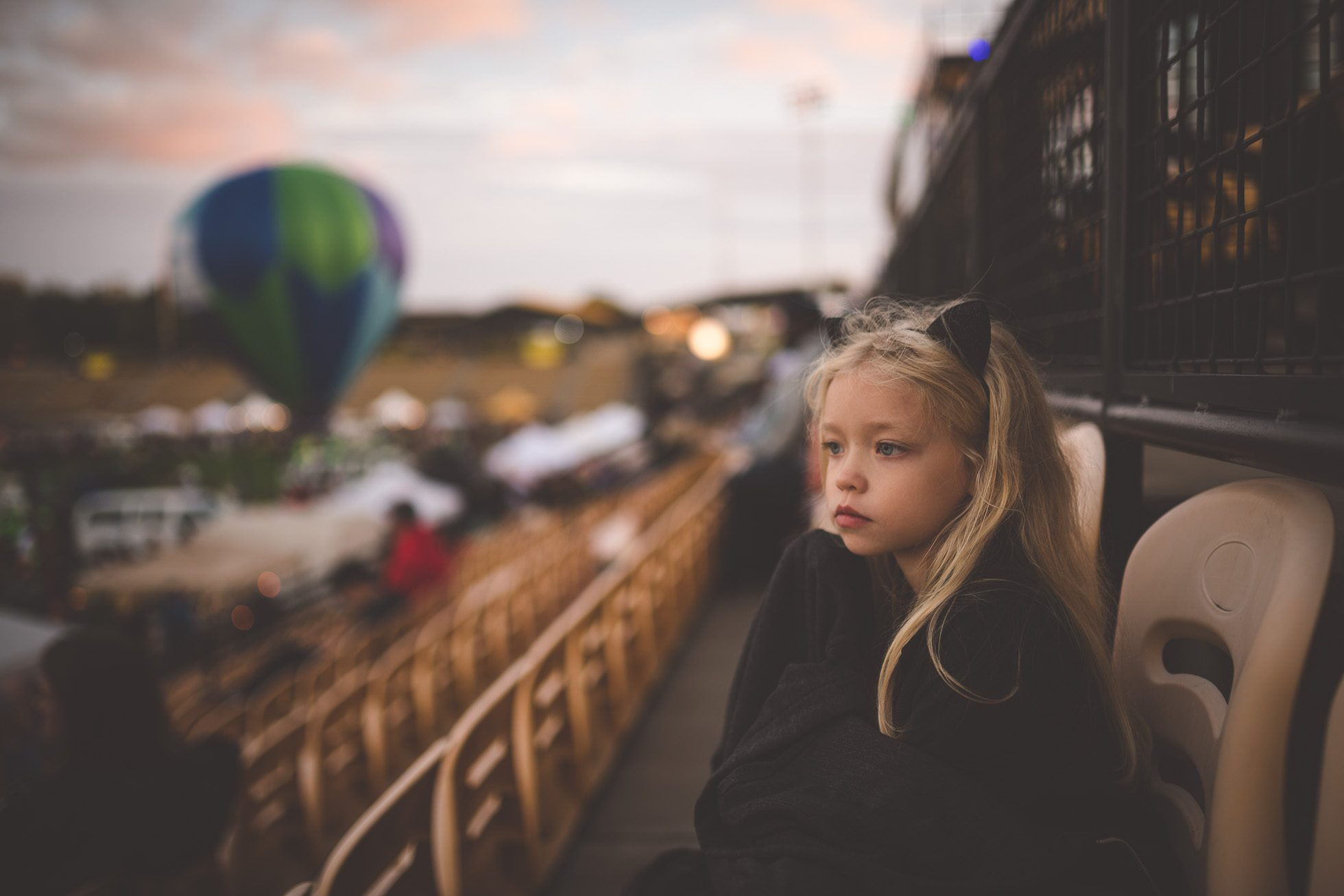 girl in cat ears watching hot air balloons