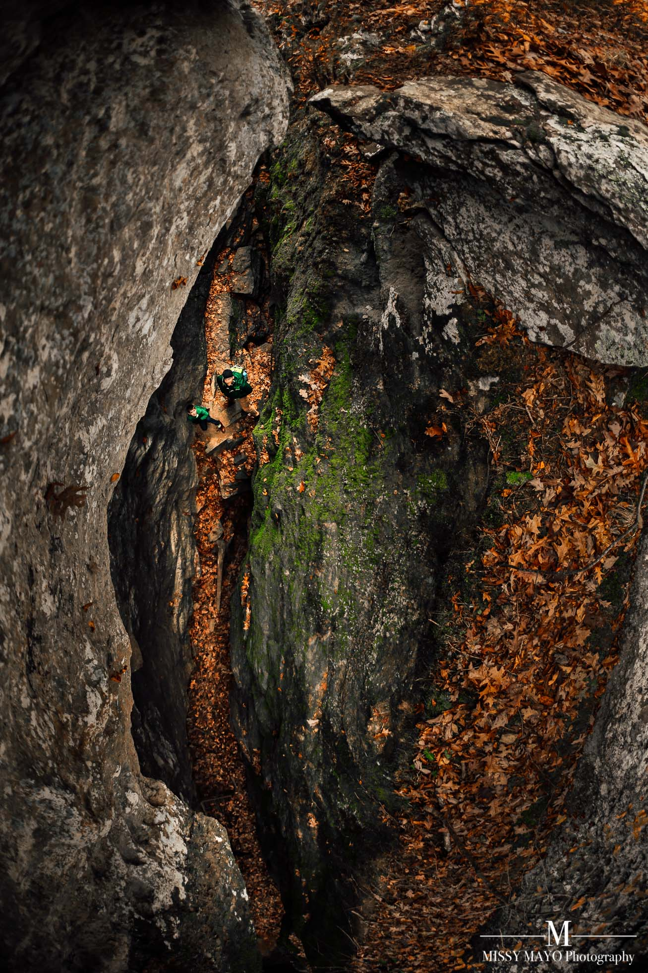 picture taken from above of two hikers exploring a rocky crevice