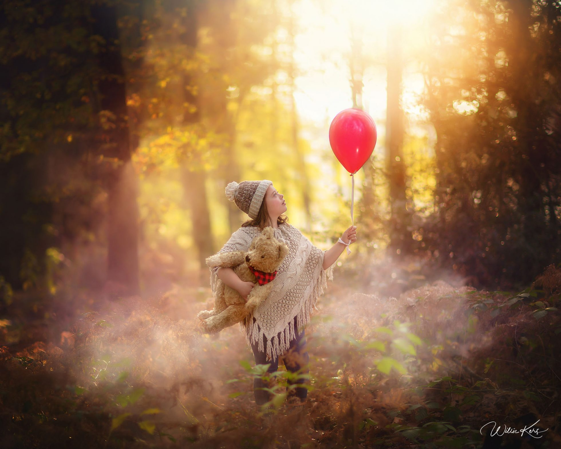 Canon 5d mark III childhood image of a girl with a red balloon with Winnie the pooh bear in her hands standing in an autumn forest during sunset by Willie Kers
