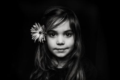 Headshot of a young girl with a flower in her hair