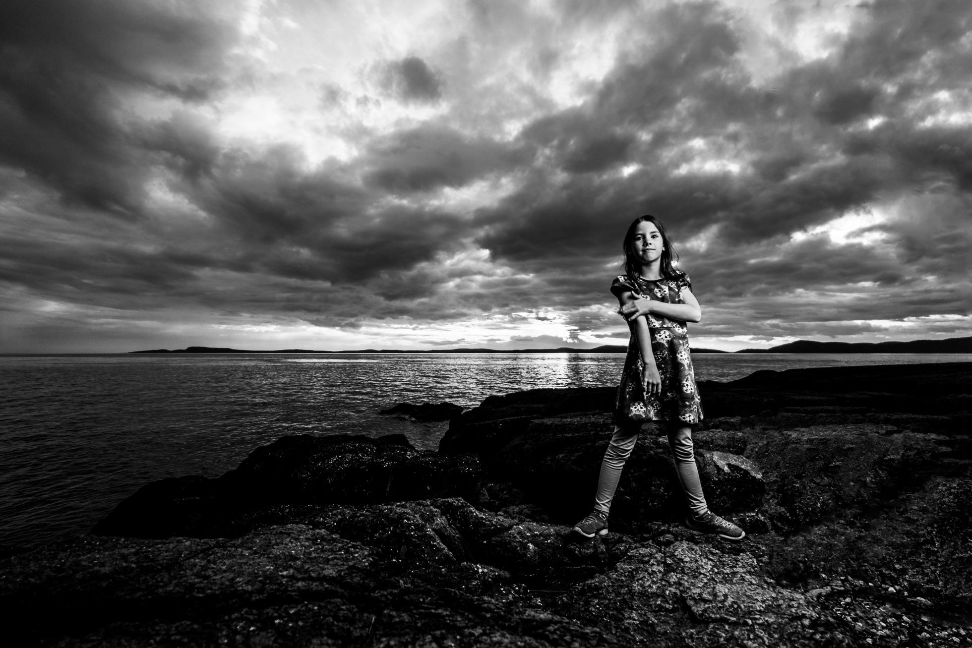 Girl on beach with storm clouds