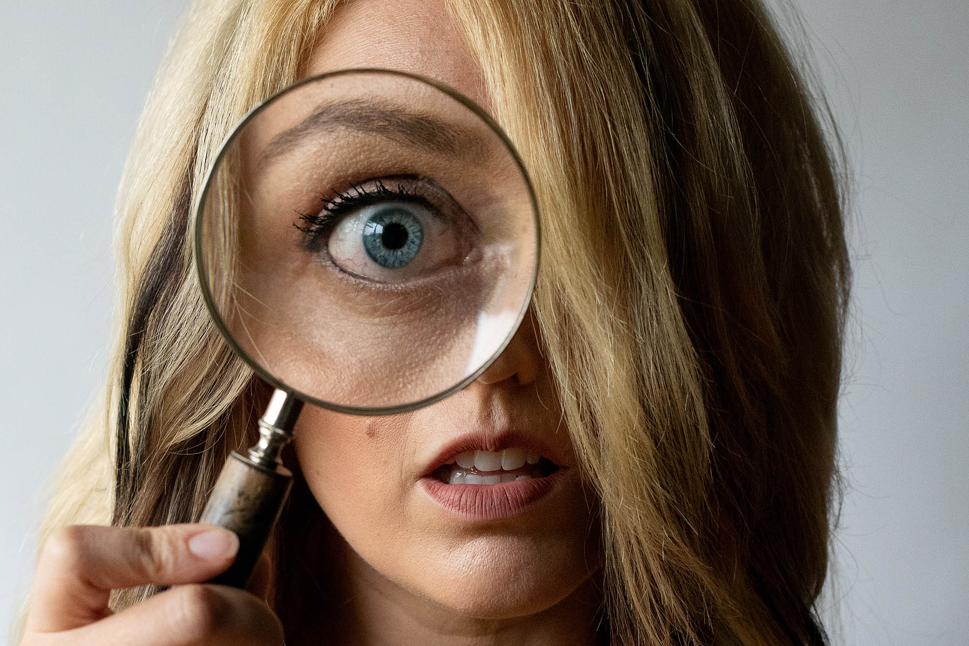 A woman's eye is greatly magnified when she holds up a magnifying glass for a self portrait