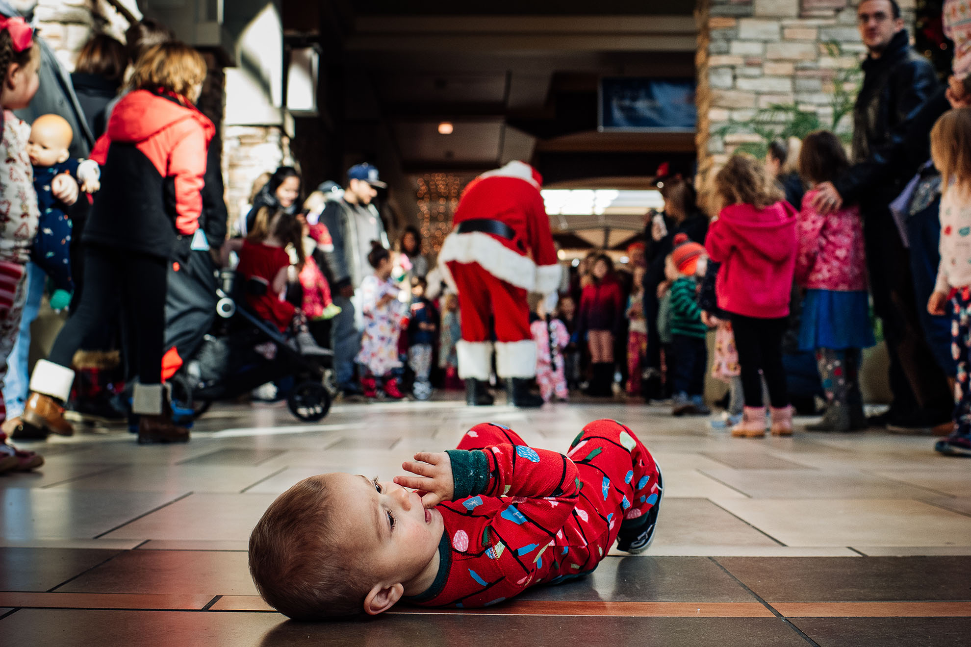 A baby lays on the floor of a mall, mid-tantrum, even though Santa is nearby.
