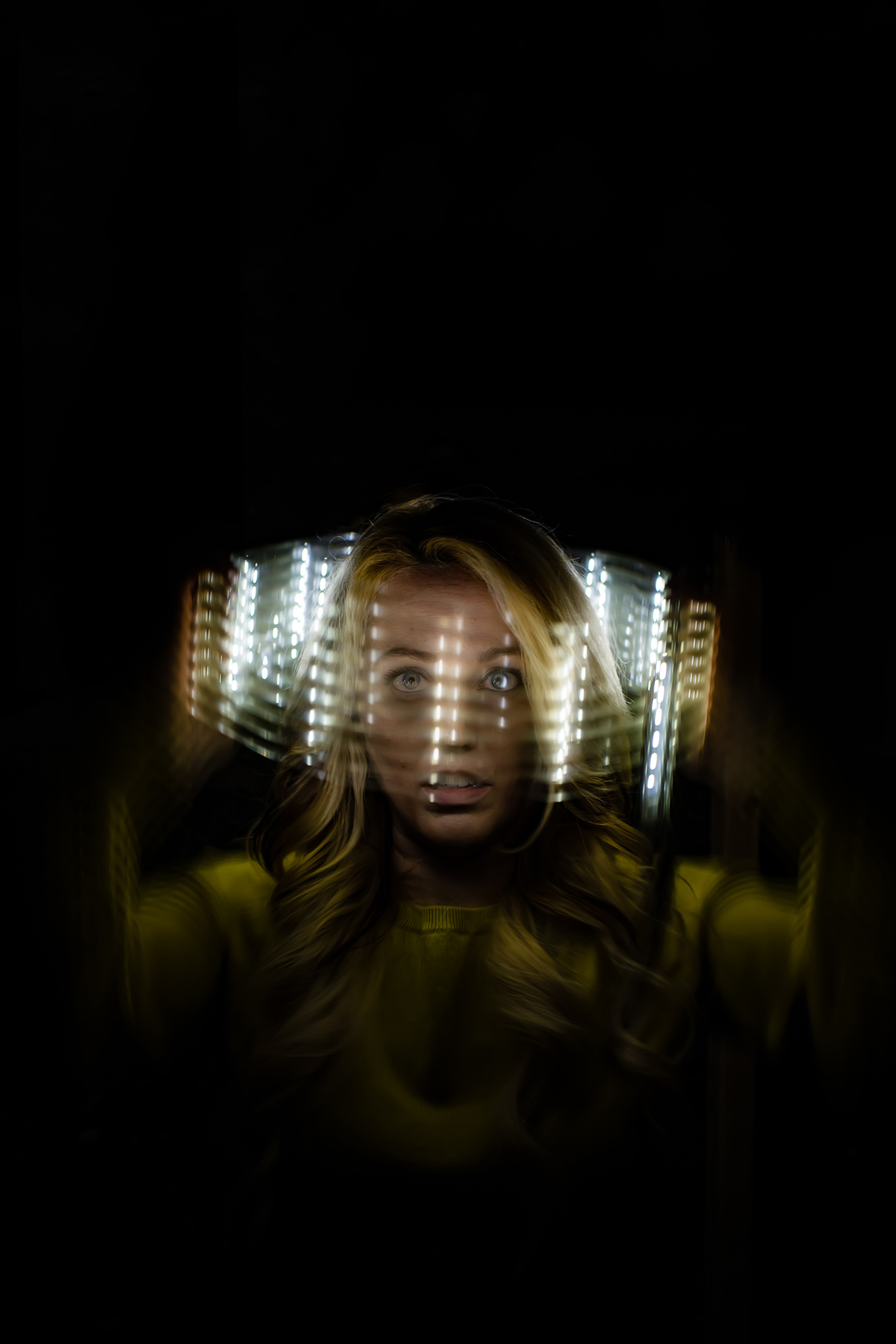 Circular light wrap around a woman's head to convey the pandemonium of thoughts in her mind.