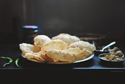 Freshly cooked poori's sit on a table top waiting to be eaten - a photo from India by Kirsty Larmour
