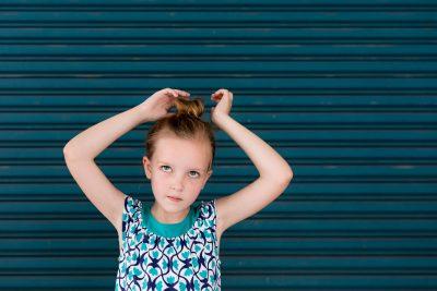 girl in teal fixing hair