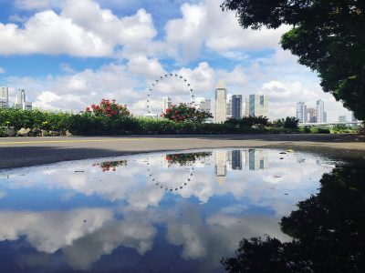 city skyline and clouds reflecting in a puddle