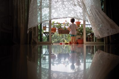 child standing framed with curtains blowing in the breeze