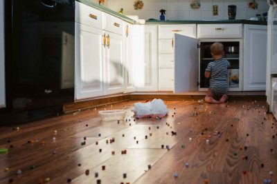 koren smith documentary photograph of a little boy playing in the kitchen after making a big mess