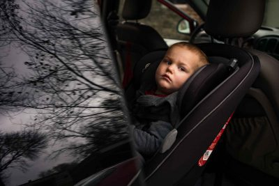 Documentary photograph of a little tired boy sitting in his car seat in a van