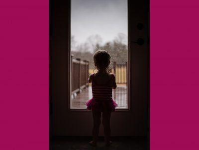 Toddler girl in swimsuit looking through window