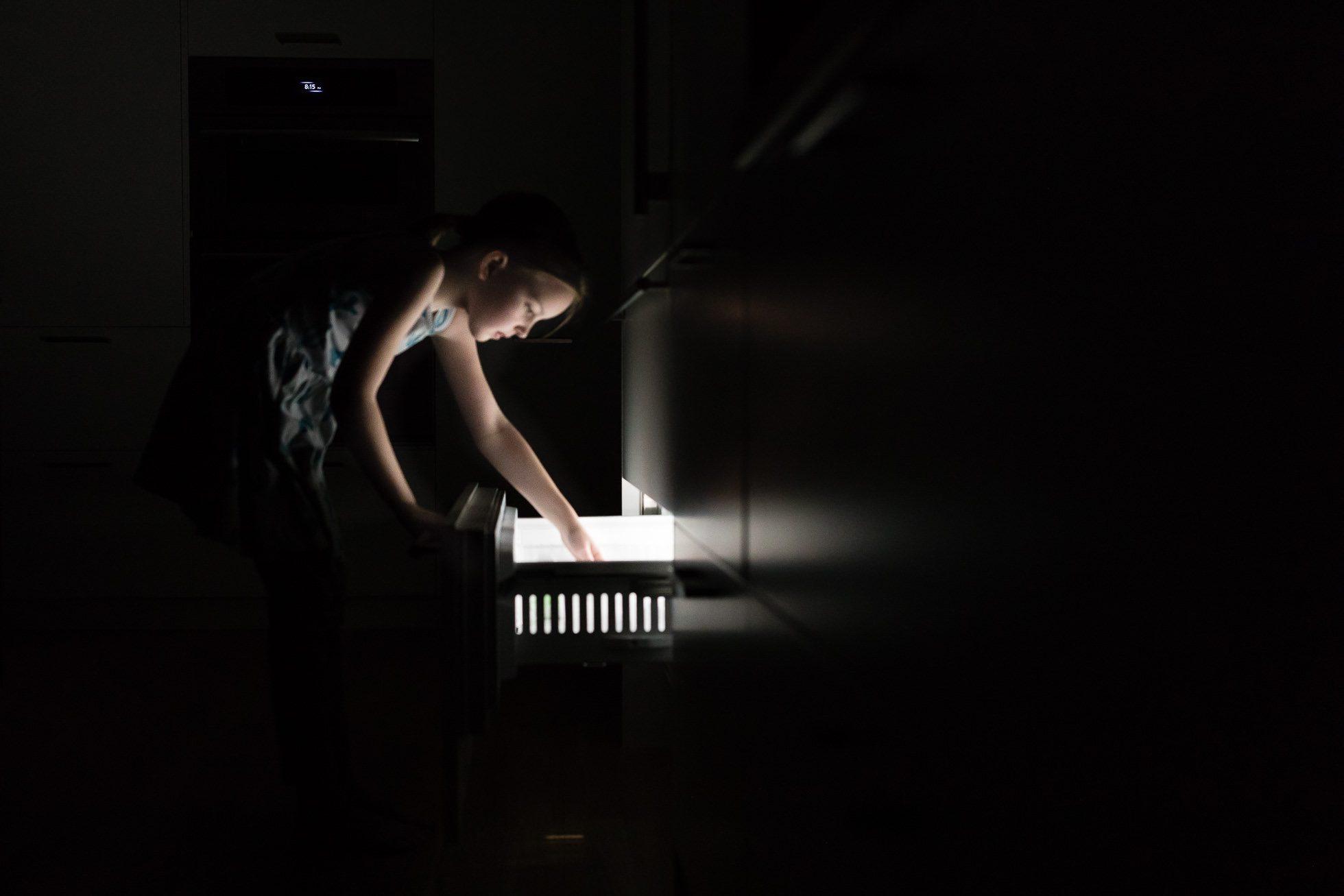 low light image of girl opening freezer drawer